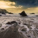 Meer überschwemmt Strand und Steine und Felsen