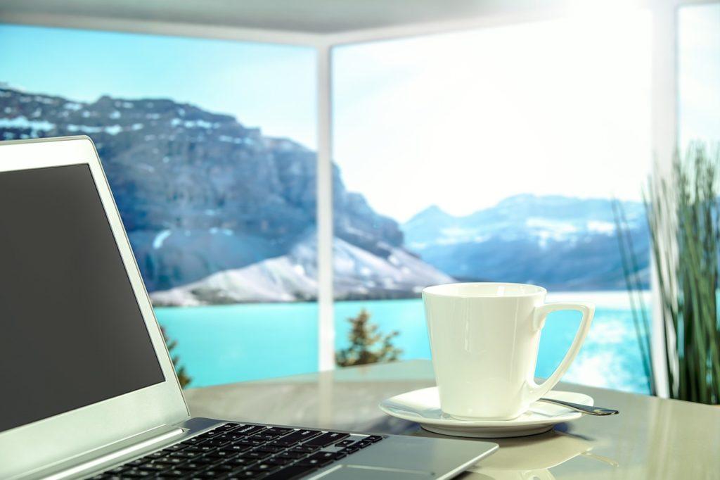 Schreibtisch, Laptop, Tasse Kaffee vor einem großen Fenster mit Ausblick auf See und Felsen - das sabische Symbol für 15-16° Wassermann