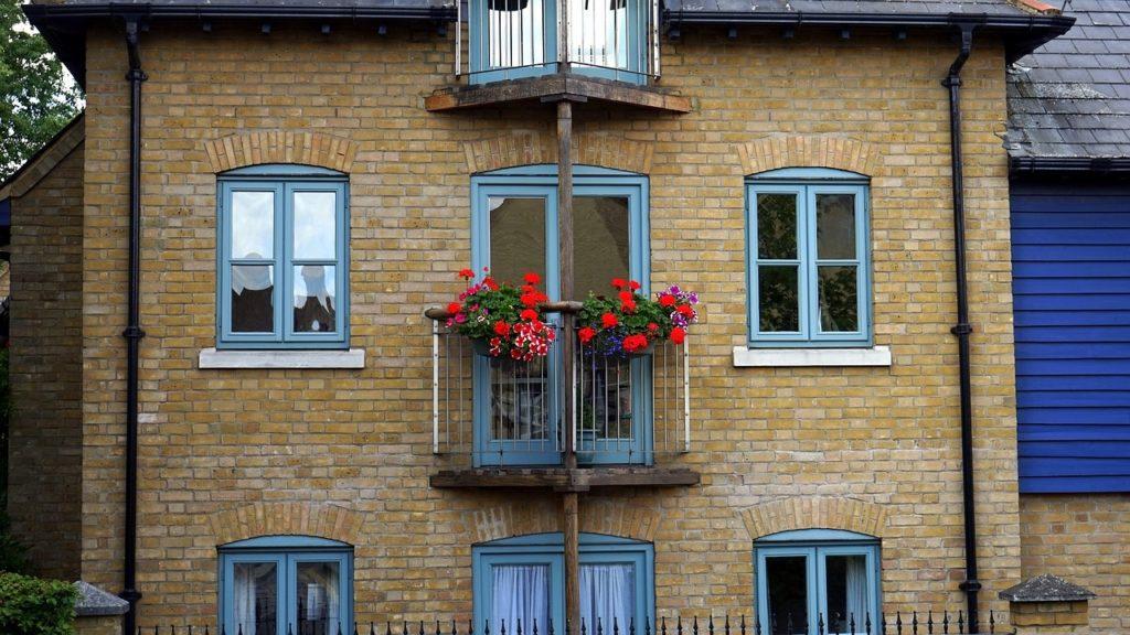 Haus mit blauen Fensterläden und Geranien auf einem Balkon